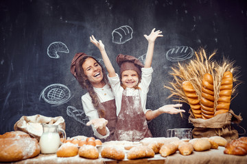 Laughing woman and little girl in aprons of cooks having fun and sprinkling flour in air standing at table