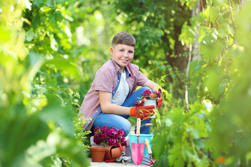 Young boy with flowers and tools in the garden