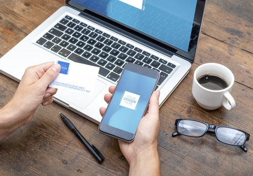 Laptop User Holding Business Card and Smartphone Mockup