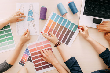 fashion designers developing new collection. creative team meeting at design studio. male and female coworkers selecting colors and sewing strings for dresses.