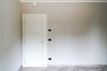 white door closed on gray wall