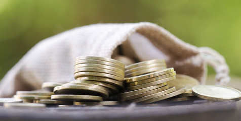 Change money - web banner of gold coins close-up with bag