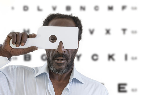 middle aged afro-american man getting eye exam at ophthalmologit bright office letter chart background