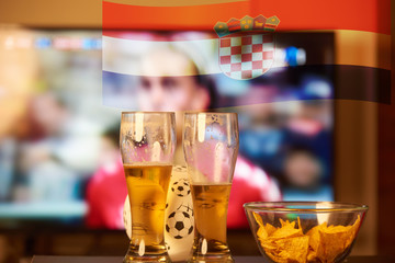 Double exposure of croatian flag and two glasses of beer in front of TV playing football