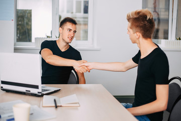 hiring new team member, celebrating success. Young modern men shaking hands while working in the creative office