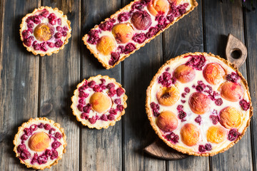 Rustic open pie with peach and raspberry, french galette . Peach tart. Raspberry tart. Tartalette with cream. Variety of bakery.