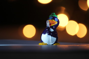 a funny pingo with an icicle toy and a beautiful bokeh in the background