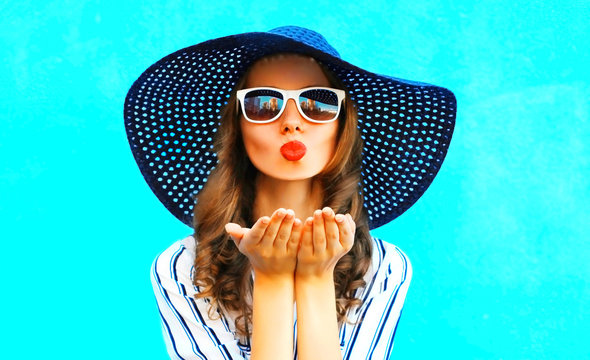 Elegant girl with red lips is sends an air kiss in straw summer hat over colorful blue background