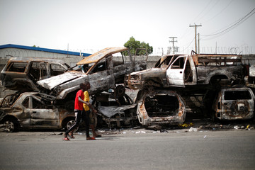 Two men walk past burnt cars piled in a street of Port-au-Prince