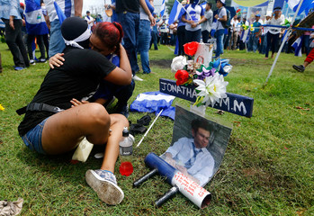 Demonstrators embrace near a memorial for university student Jonathan Morales during a march called against Nicaragua's President Daniel Ortega's government, in Managua