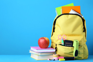 Yellow backpack with school supplies on blue background