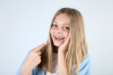 Young smiling girl with dental braces on grey background