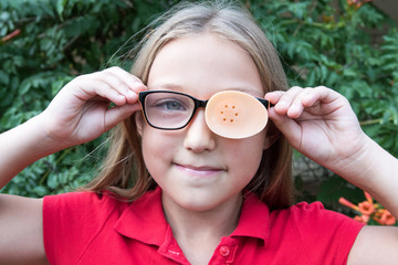 .Child in glasses with Occluder. Ortopad Girls Eye Patches nozzle for glasses for treating strabismus (lazy eye)