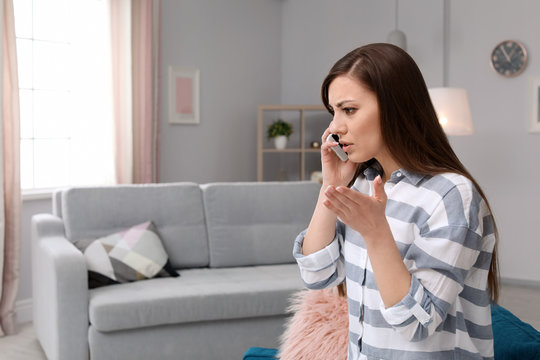 Woman arguing on mobile phone at home
