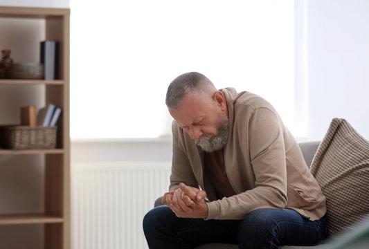Depressed senior man sitting on sofa indoors