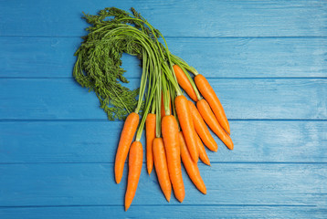 Ripe carrots on wooden background, top view