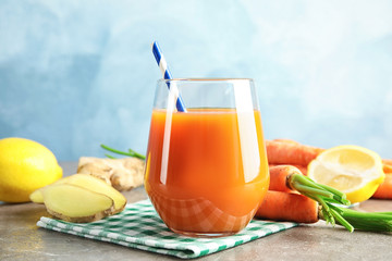 Glass with carrot juice and fresh ingredients on table