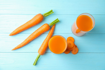 Glasses with carrot juice and fresh vegetable on wooden table, top view