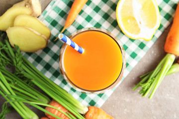 Glass with carrot juice and fresh ingredients on table, top view