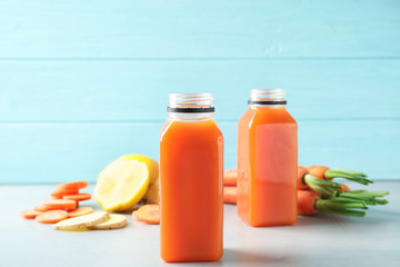 Bottles with carrot juice and fresh ingredients on table
