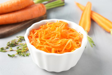 Bowl with grated ripe carrot on table