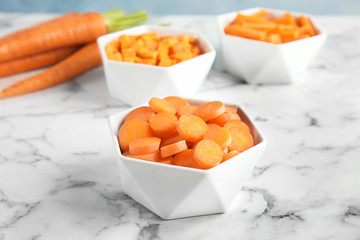 Bowl with cut ripe carrot on table