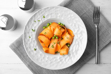 Tasty salad with fresh carrot in plate on table, top view