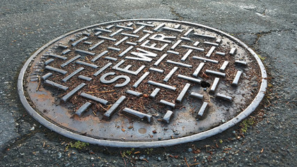 Sewer metal cap on the road after rain in close up