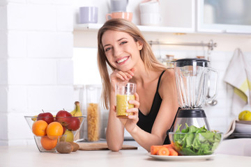 Young woman with glass of tasty healthy smoothie at table in kitchen