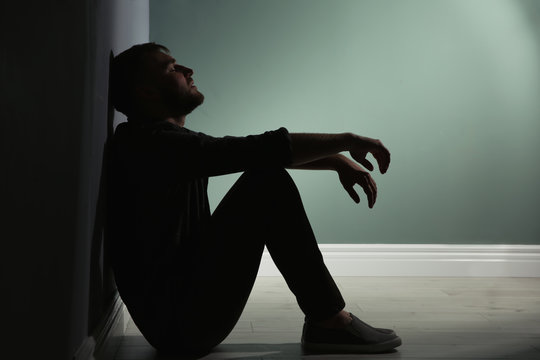 Depressed young man sitting on floor in darkness
