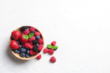 Photo sur Plexiglas Fruit Bowl with raspberries and different berries on wooden table, top view