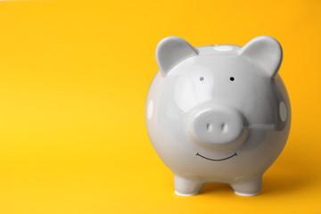 Gray piggy bank on color background. Money saving