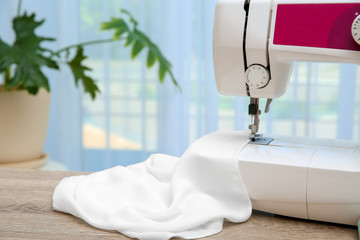 Sewing machine with textile on table near window