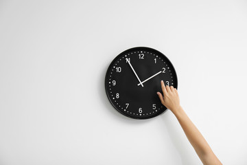 Woman pointing on clock against white background. Time concept
