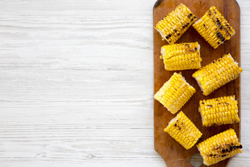 Top view, grilled corn on the cob on rustic wooden board over white wooden background. Summer food. From above, overhead. Copy space.