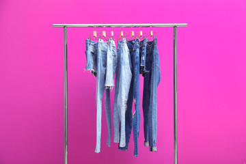 Rack with stylish jeans and denim shorts on color background