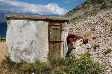 Small concrete fisherman shed with peeling plasterwork and rusty doors with laminate fishing boat placed behind. Located in small rocky bay in Croatia, Adriatic