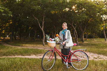 Smiling girl with red bicycle and basket full of wildflowers and fruits happily looking in camera holding orange in hand