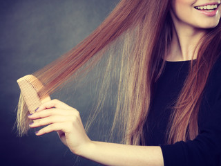 Long haired girl combing her beauty hair.