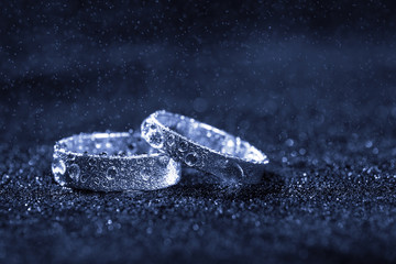 Two wedding rings with water drops on blue background with copy space.