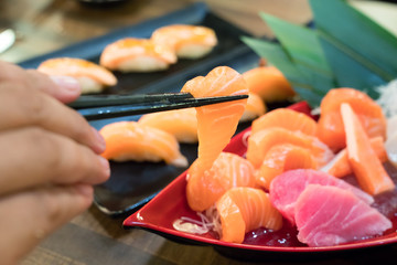 Chopsticks with Salmon sashimi with Mixed sliced fish sashimi on ice in black bowl. Japanese food in Asian restuarant.