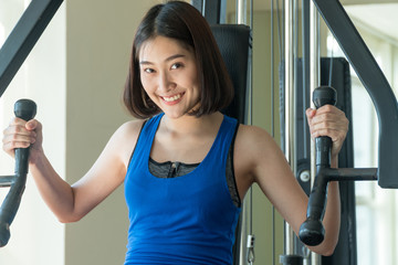 Young women exercising on machine in the gym. Happy muscular fit women workout looking at camera on fitness center.