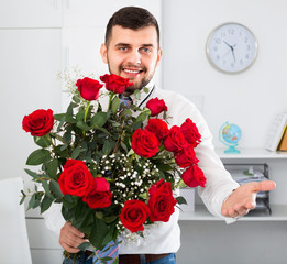 Young man ready to present flowers to woman
