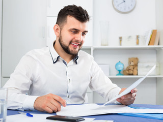 Smiling young man signing profitable financial agreement