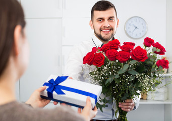 Man ready to present flowers and gift at holiday