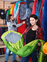 Woman shoosing new sleeping bag