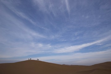 Silhouetted figures on sand dunes, Xinjiang, China