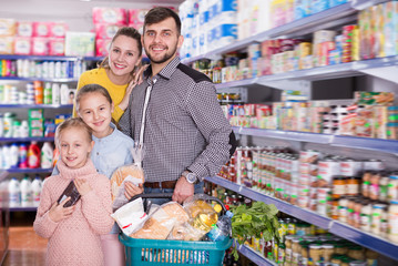 Glad friendly family of four with full basket