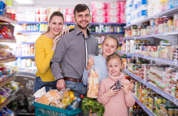 Cheerful family of four with full basket