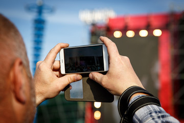 Man holding smartphones in hands and photographing. Taking photo on summer outdoor music concert festival.